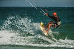 Man Kitesurfing i det blåa havet Arkivfoton