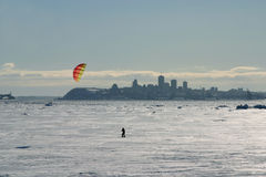 Man kiting. On snow with city in background Stock Photography