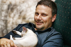 Man and kitten. A man relaxing with a sleeping Siamese kitten Royalty Free Stock Image
