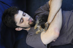 Man and Kitten. A young man with a small blue-eyed kitten falling asleep on his chest Royalty Free Stock Images