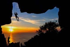 Man klättringen i grottan på berget Arkivbild