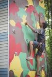 Man klättringen på konstgjort vaggar den bärande säkerhetsselet sui för klippan arkivfoton