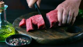 Man klippt rått nötkött på biffstycken arkivfilmer