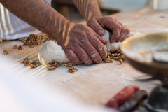 Man knead the dough. Male hands knead the dough for a white bread with walnuts stock photo