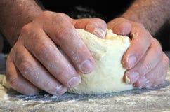 Man knead dough. Man`s hands knead dough on a kitchen top Stock Photos