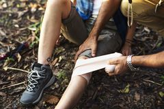 Man with knee injury while trekking. Woman with knee injury while trekking Royalty Free Stock Image