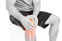 Man with knee pain sitting against white background Stock Photo