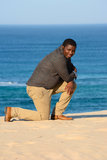 Man kneeling on beach Stock Images