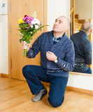 Man kneeling with  bouquet of flowers. Stock Photo