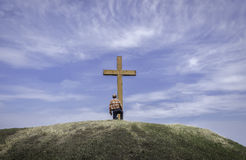 Man kneeling by a cross on a hill in summer time. Horizontal image of a man kneeling by a wooden cross on a grassy hill surrounded by a beautiful blue sky with Royalty Free Stock Images
