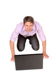 Man kneeling in front of laptop. Royalty Free Stock Photography
