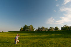 Man kneeling in the middle of huge meadow Royalty Free Stock Images