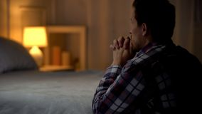 Man kneeling near bed and praying to god, thanking for life opportunities. Stock photo royalty free stock image