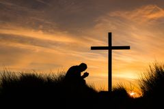 In Prayer Cross Sunset. Man kneeling in pray on top of a hill by a cross at sunset Royalty Free Stock Images