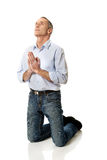 Man kneeling and praying to God Stock Photo