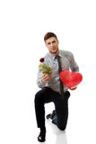 Man kneeling with red rose and heart balloon. Royalty Free Stock Photography