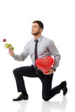 Man kneeling with red rose and heart balloon. Stock Images