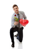 Man kneeling with red rose and heart balloon. Young happy man kneeling with red rose and heart balloon Royalty Free Stock Photos