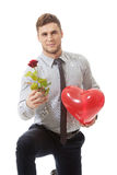 Man kneeling with red rose and heart balloon. Royalty Free Stock Images