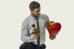Man kneeling with red rose and heart balloon. Young happy man kneeling with red rose and heart balloon Royalty Free Stock Photo