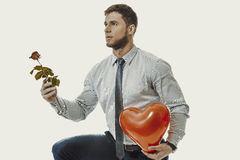 Man kneeling with red rose and heart balloon. Young happy man kneeling with red rose and heart balloon Stock Images