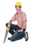 Man kneeling with saw Royalty Free Stock Image