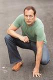 Man kneeling in the street Stock Photo