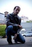 Man kneeling on street Royalty Free Stock Photo