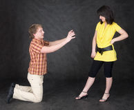 Man is kneeling to the young woman Royalty Free Stock Image