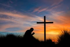 Prayful Man By Cross. Man kneeling on top of a hill praying by a cross at sunset royalty free stock photos