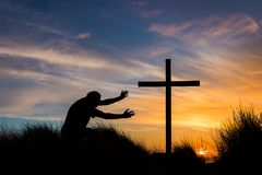 Reach for Salvation Cross. Man kneeling on top of a hill reaching for a cross at sunset Royalty Free Stock Photography