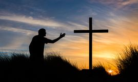 Reach for Salvation. Man kneeling on top of a hill reaching out to a cross at sunset Royalty Free Stock Photo