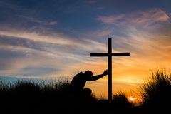 Touch The Cross. Man kneeling on top of a hill touching a cross at sunset Royalty Free Stock Photo