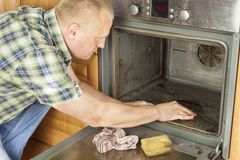 Man kneels on the floor in the kitchen and cleans the oven. Royalty Free Stock Photography