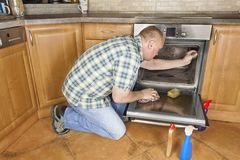 Man kneels on the floor in the kitchen and cleans the oven. Stock Photo