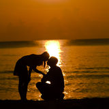Man knees ask woman to marry. On the beach in the morning Stock Photos