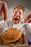 Man with knife and fork eating burger. Portrait of happy man with knife and fork eating burger stock image