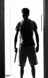 Man with knife silhouette. Man with a knife standing in doorway staring Royalty Free Stock Photography