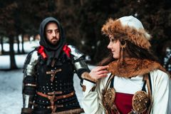 Man knight in armor and woman in historical costume. Man knight in armor and women in historical costume in the forest in winter stock images