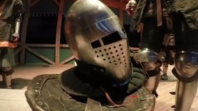 Man in knight armors standing by bench with helmet on it, reenactment of events. Stock footage stock video