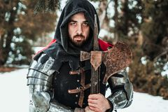 Man knight in historical clothing with an ax. Male knight in historical clothing with an ax in the woods in winter stock photo
