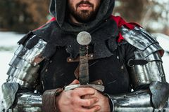 Man knight with a sword. Bearded man knight in iron armor with a sword stock image