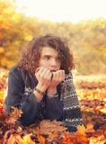 Man in knit sweater and scarf lying on autumn leaves, oudoor in autumn park. Royalty Free Stock Photography