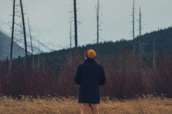 Man in Knitted Cap and Black Coat Fronting Forest Trees and Mountain during Daytime Royalty Free Stock Photography