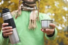 Man in knitted scarf, offers hot drink - tea or coffee from thermos to someone, front view stock photo