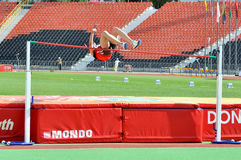 Man knocks the bar during high jump Stock Photography