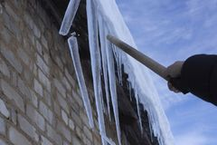 Man knocks icicles with a stick royalty free stock photo