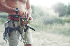 A man Knots a knot on a climbing harness. A man climber Knots a knot on a climbing harness. hands in chalk close up royalty free stock image