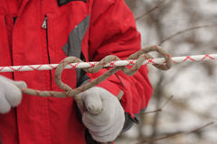 Man knotting a rope Stock Photo