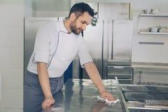Man kocken för den japanska restaurangen som arbetar i köket Royaltyfri Bild